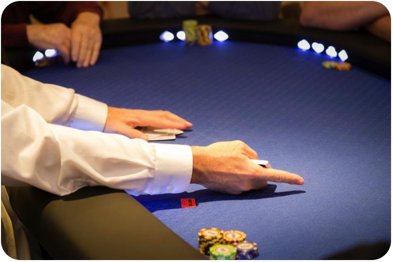 Un croupier distribue les carte des joueurs pré flop