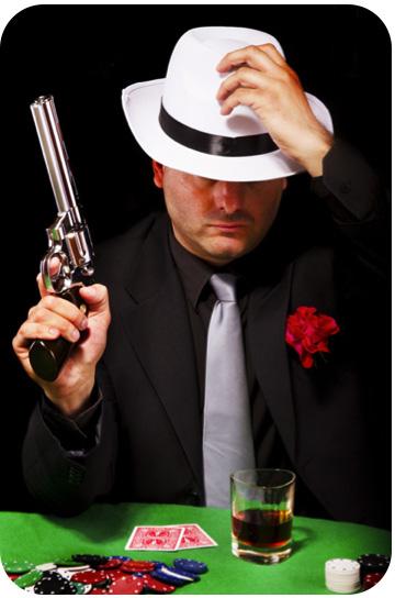 Un homme assis a une table de poker et tenant un pistolet